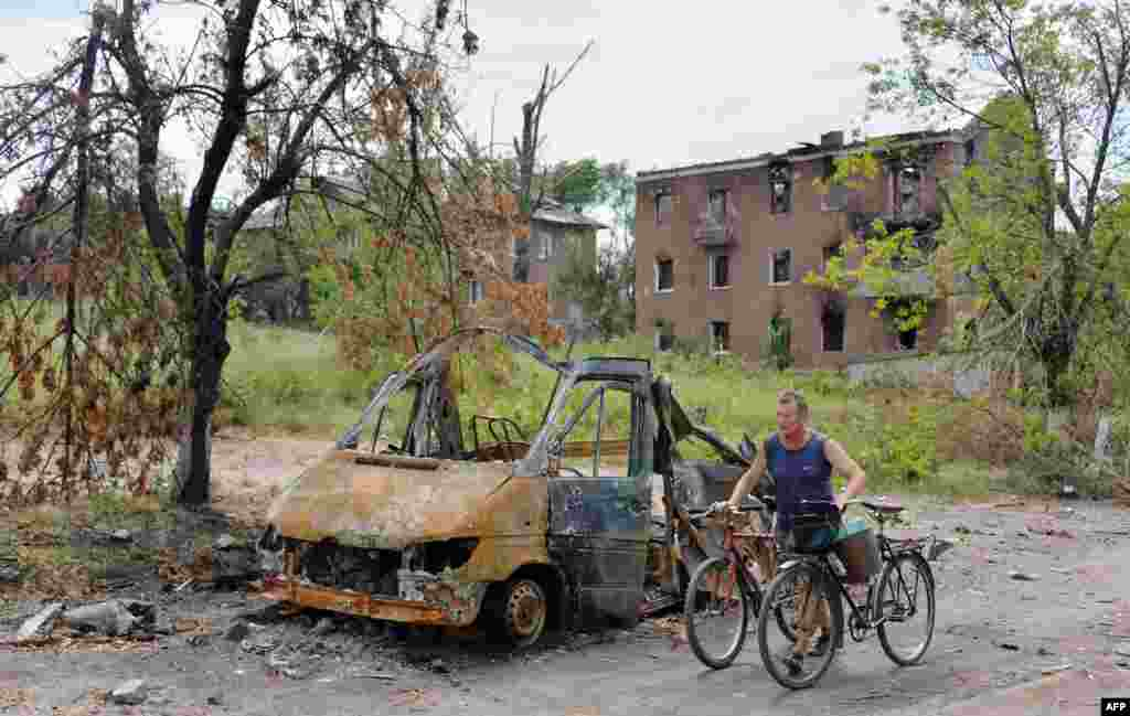 A resident pushes two bicycles past a burnt vehicle in the village of Semenivka, near Slovyansk, Ukraine, on July 13. (AFP/Genya Savilov)
