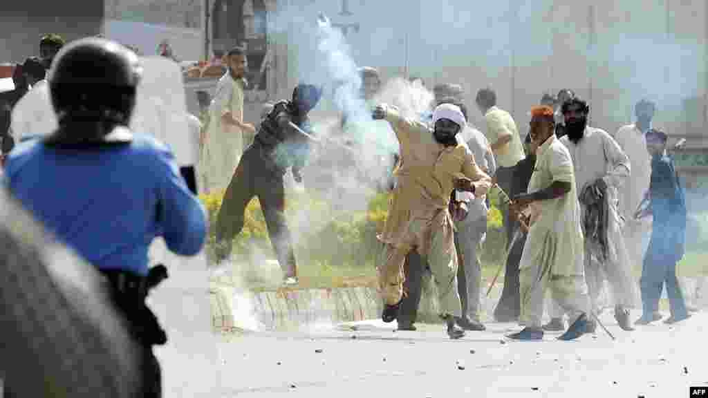 A demonstrator throws a tear-gas shell toward riot police during a protest against an anti-Islam film in Islamabad on September 21.