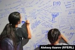 Посетители выставки пишут на стене воспоминаний. Алматы, 26 августа 2018 года.