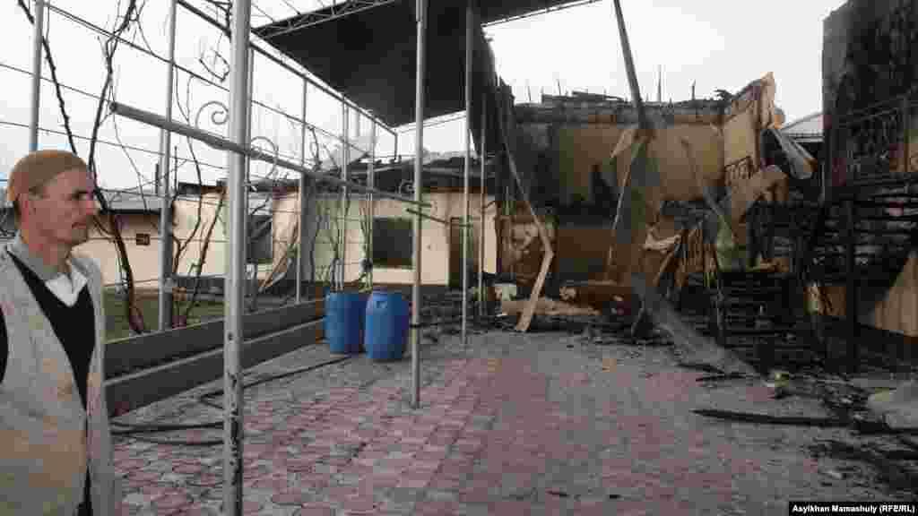 Житель села Ынтымак у горевшего дома.