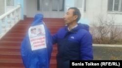 Активист Бекболат Муханбетали с курткой с изображениями Макса Бокаева и Талгата Аяна стоит перед зданием суда. Атырау, 15 ноября 2016 года.