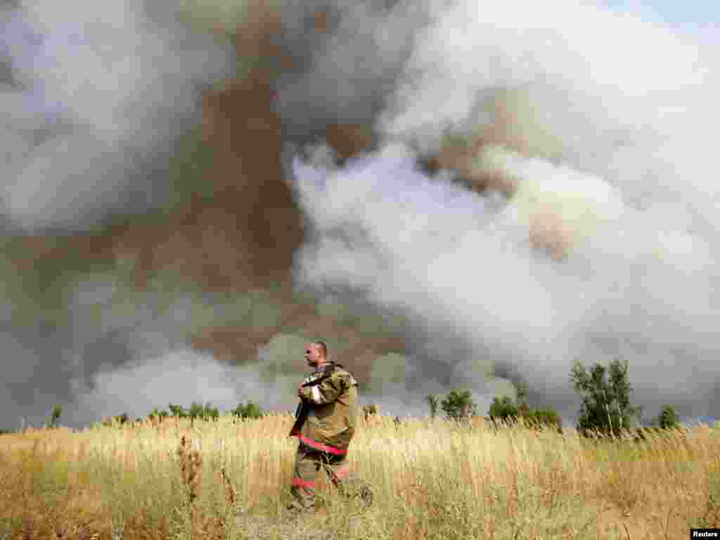 A firefighter walks in a field while smoke from a wildfire clouds the air outside the settlement of Kustarevka in the Ryazan region, some 340 kilometers southeast of Moscow, on August 10. Photo by Denis Sinyakov for Reuters