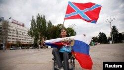 Мужчина держит флаг так называемой «Новороссии» (сверху) и России (внизу) во время митинга на площади Ленина в оккупированном Донецке, 13 июля 2014 года