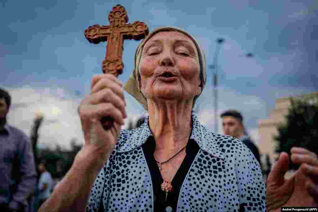 A woman prays during a protest against the Romanian government's coronavirus measures in Bucharest on July 12. (AFP/Andrei Pungovschi)