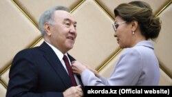 Председатель сената парламента Казахстана Дарига Назарбаева награждает своего отца, экс-президента Казахстана Нурсултана Назарбаева знаком почетного сенатора. Нур-Султан, 6 июля 2019 года.