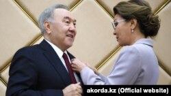 Дарига Назарбаева вручает своему отцу – Нурсултану Назарбаеву – знак почетного сенатора Казахстана.