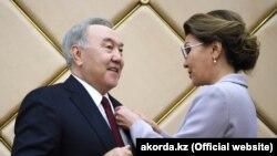 Дарига Назарбаева вручает своему отцу, бывшему президенту Казахстана Нурсултану Назарбаеву, значок «почетного сенатора». Нур-Султан, 6 июня 2019 года.