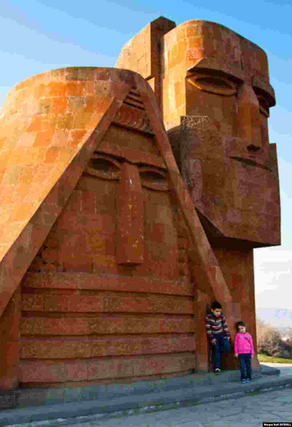"Kids pose by a monument titled ""We Are Our Mountains,"" informally known as ""Grandma and Grandpa."" The 1967 sculpture is recognized as a symbol of Nagorno-Karabakh."