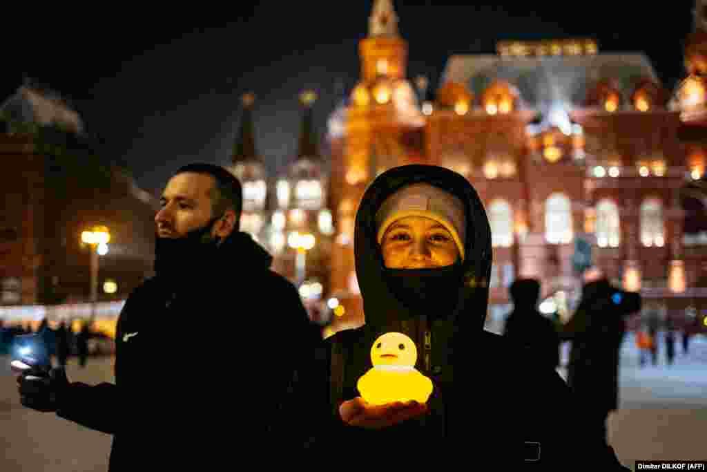 O femeie pozează cu o rață de plastic strălucitoare lângă Piața Roșie din Moscova pe 14 februarie. Rața este o referință la acuzațiile potrivit cărora fostul prim-ministru (și președinte cu un mandat) Dmitri Medvedev are o proprietate de lux cu un lac privat și un adăpost pentru păsările acvatice.
