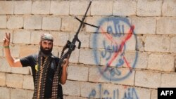 An Iraqi Shi'ite fighter flashes the victory sign in front of graffiti of the Islamic State group in the town of Baiji on June 9.