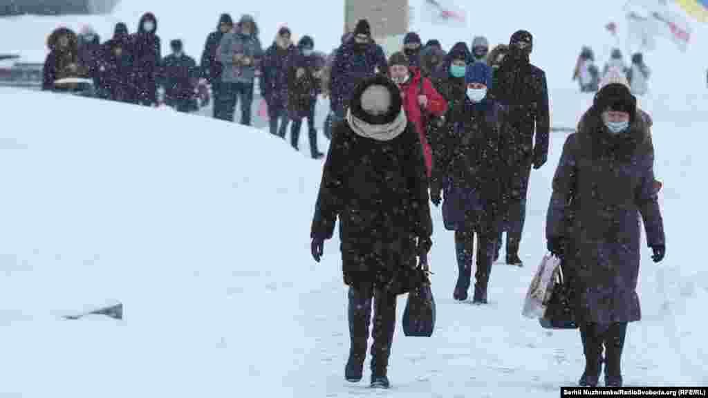 Люди йдуть від метро в центральній частині міста