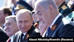 Ресей президенті Владимир Путин (ортада) мен Израиль премьер-министрі Биньямин Нетаньяху (оң жақта) Қызыл алаңдағы парад кезінде. Мәскеу, 9 мамыр 2018 жыл.