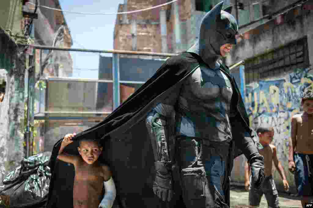 A child plays under the cape of a man in a Batman costume in the Favela do Metro slum area, near Maracana Stadium in Rio de Janeiro, where shanties are being leveled to renovate the area ahead of the Brazil's hosting of the FIFA World Cup in June. (AFP/Yasuyoshi Chiba)