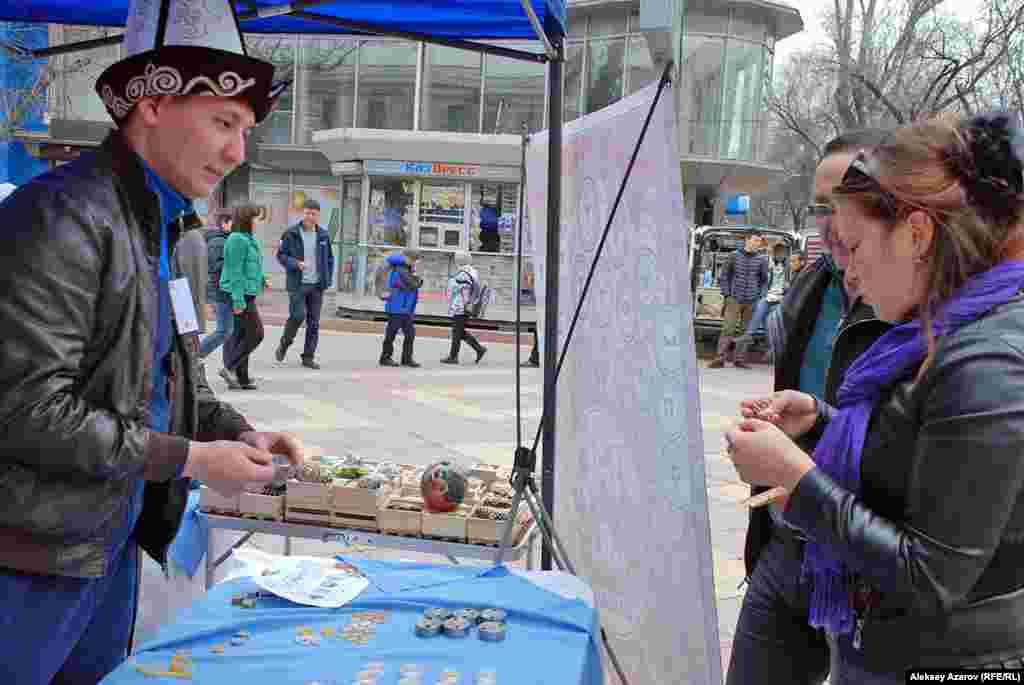 Молодой мужчина предлагает сувенирные монеты ручной холодной чеканки. Чеканка производится на месте.