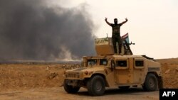 A member of Iraqi government forces flashes the sign for victory as he stands on a military vehicle while smoke billows from oil wells set ablaze by Islamic State militants before they fled the region of Qayyarah late last month.