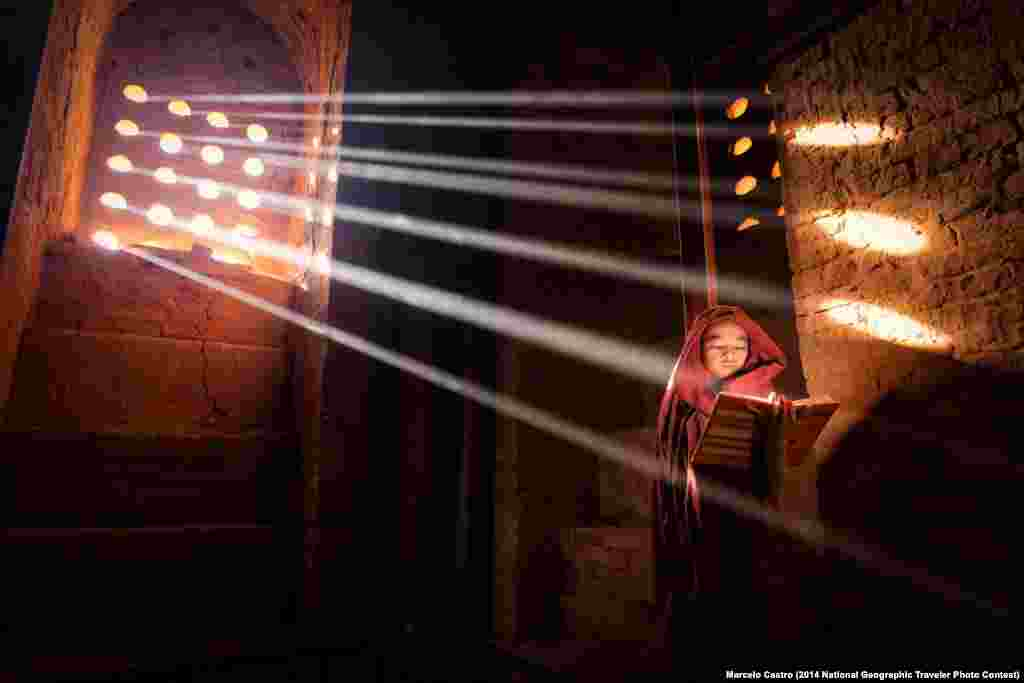 """LightSource,"" by Marcelo Castro. Old Bagan, Burma. ""Young Monk finds a perfect light source to read his book inside of his pagoda."""