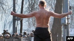 A shirtless man waves a Ukrainian flag during clashes between the opposition and police in downtown Kyiv on January 20.