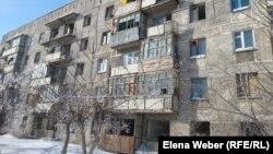 Разваливающийся дом, в котором заселены лишь несколько квартир. Поселок Актау Карагандинской области, 6 марта 2015 года.