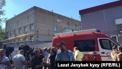Журналисты и пожарные перед зданием склада, где погибли 17 человек