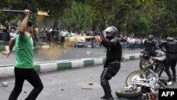یک مأمور گارد ویژه در حال استفاده از اسپری فلفل در مقابل یکی از معترضان