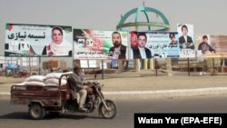 Election campaign posters are installed on a road side ahead of the upcoming Parliamentary elections, in Helmand, October 8, 2018