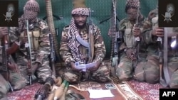 A man claiming to be the leader of Nigerian Islamist extremist group Boko Haram, Abubakar Shekau, is seen in this video from September 2013 flanked by armed men.