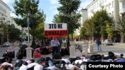 """В центре массовки появился человек, одетый в черное и олицетворявший террориста-смертника. Раздался взрыв (петарды), и участники флешмоба рухнули на землю. Стоять остался только молодой человек с окровавленным лицом, в разодранной одежде с трафаретом в руках. Двусторонняя надпись гласила: """"Убивать мирных людей – это не джихад!"""