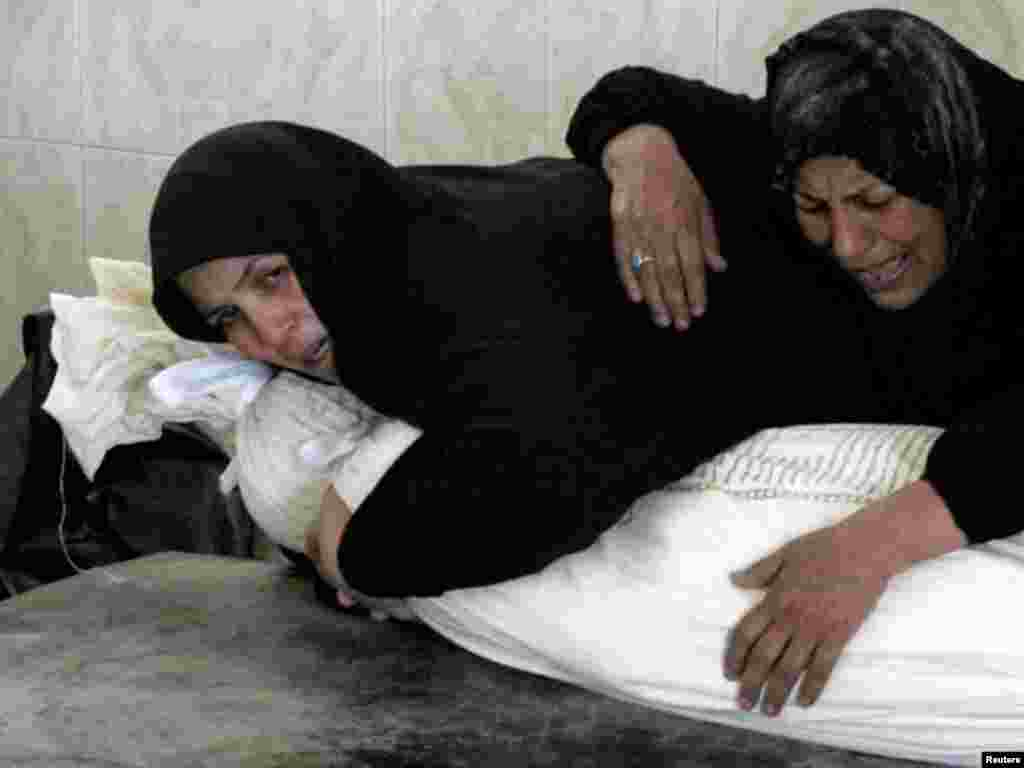 Two women mourn over the shrouded body of a victim of bomb attacks before his burial at a cemetery in Najaf, south of Baghdad, on August 26. Suicide bombers and other attackers killed at least 62 people in coordinated attacks on Iraqi security forces throughout the country on August 25, less than a week before U.S. troops formally end combat operations. Photo by Ali Abu Shish for Reuters