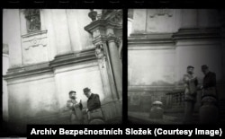 Two men chatting at the entrance of a church near Prague Castle.