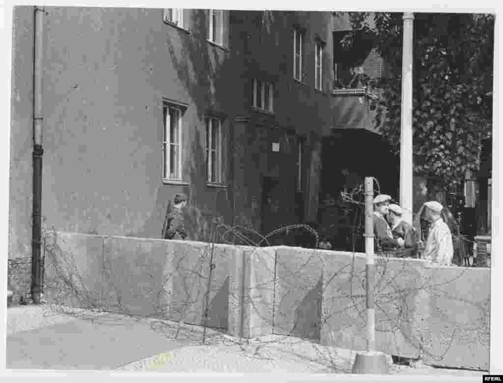 A section of the temporary wall snaking through Berlin. In the first week of the division of Berlin, East German authorities erected a barbed-wire fence, laid concertina wire, and mounted heavily armed patrols. The construction of the real wall would begin in the next week or so.