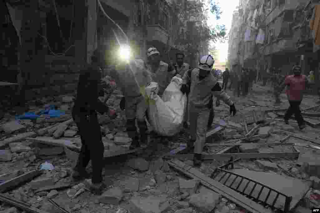 Syrian emergency personnel carry a body following an air strike, in the rebel-held side of the northern city of Aleppo on November 3. (AFP/Baraa al-Halabi)