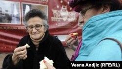 Ljudi jedu hleb na ulici u Beogradu, tokom lomljenja božićnog kolača, ilustrativna fotografija