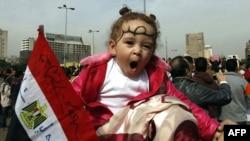 Юная египтянка одна из сотен тысяч демонстрантов, пришедшая на площади Тахрир на плечах своей матери. 1 февраля 2011 года