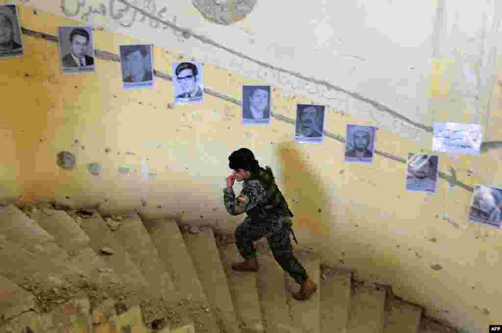 An Afghan soldier walks past photographs of victims of war on display to mark Human Rights day at the ruined Darlaman Palace in Kabul on December 10. (AFP/Aref Karimi)