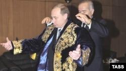 Президент Узбекистана Ислам Каримов надевает чапан на Владимира Путина, в то время - премьер-министра России. 12 декабря 1999 года.