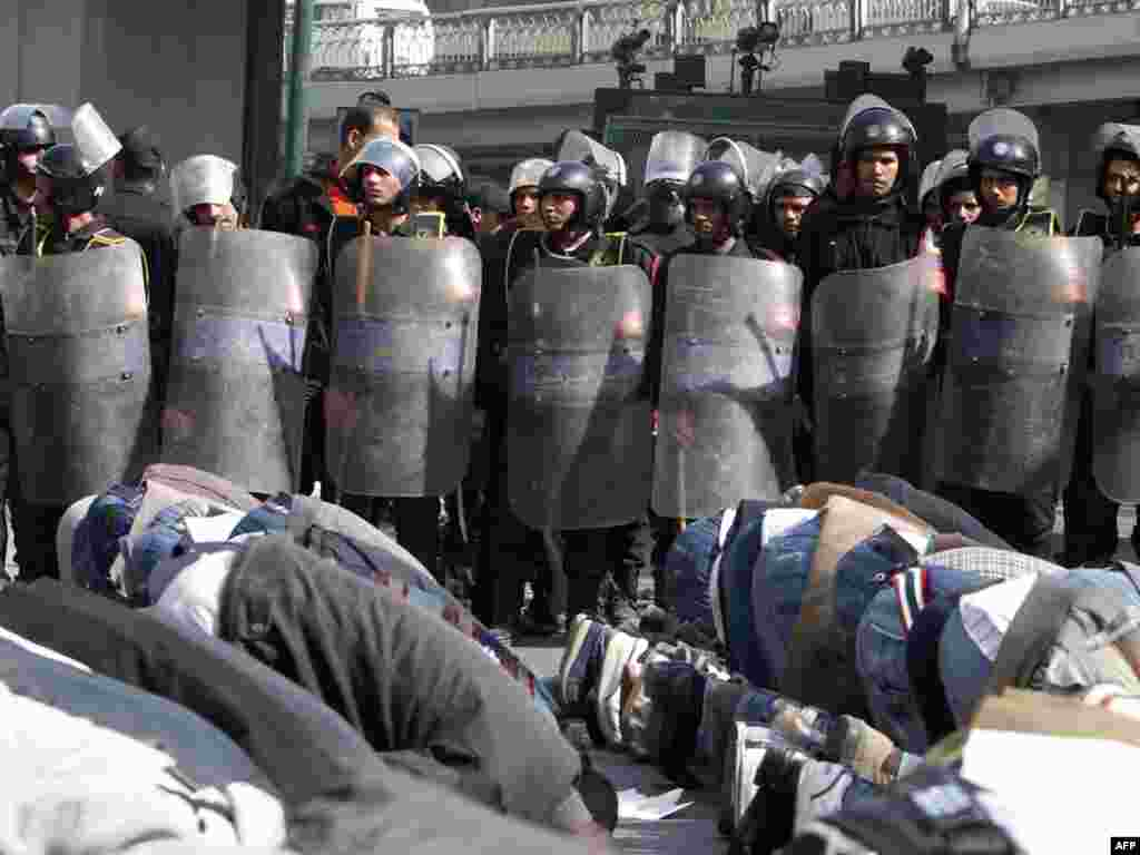 Demonstrators perform Friday Prayers in front of riot police during a demonstration in Cairo on January 28.