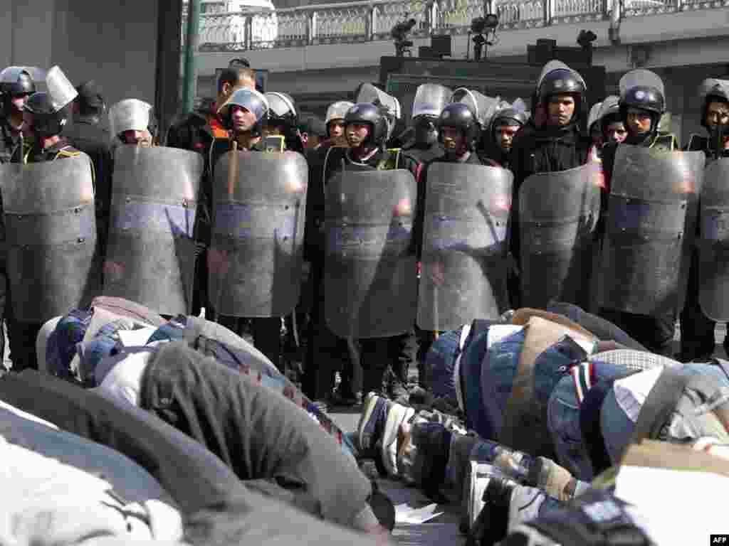Протестующие участвуют в пятничной молитве прямо на митинге перед полицией. Каир, 28 января 2011 года
