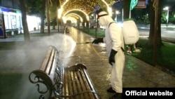 Рабочий в защитном костюме обрабатывает скамейку на улице в Худжанде. 28 апреля 2020 года.