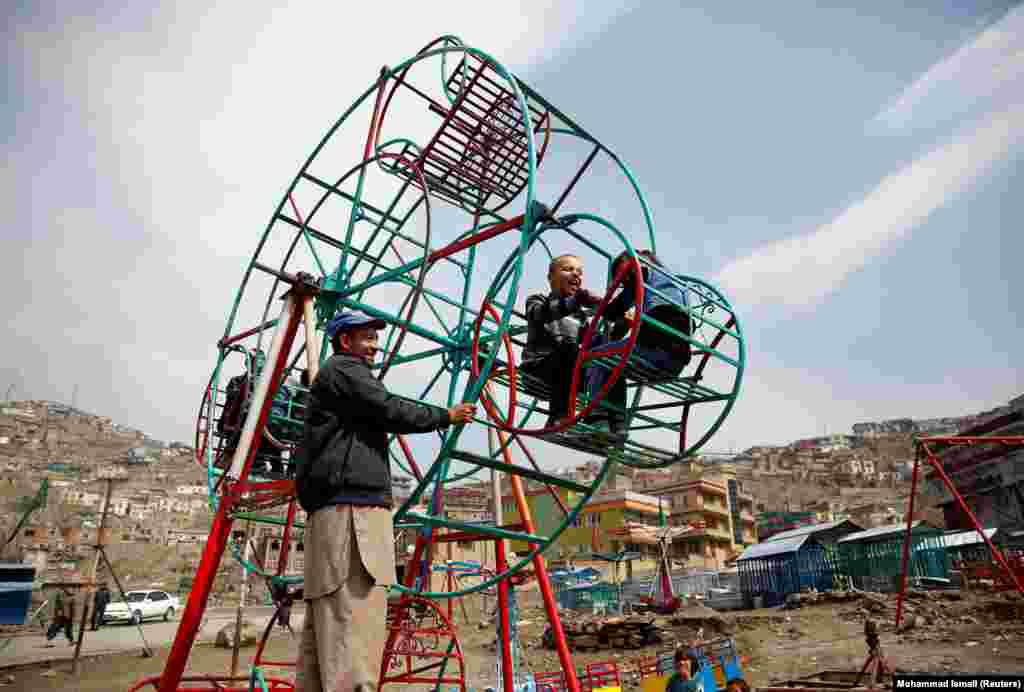 Children enjoy a manually operated Ferris wheel in Kabul. (Reuters/Mohammad Ismail)