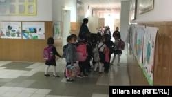 Учитель и ученики в коридоре средней школы.