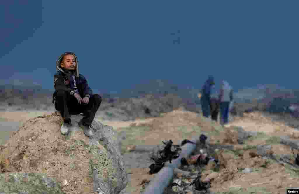 Мальчик сидит на камне и смотрит вдаль - на охваченное огнем месторождение.