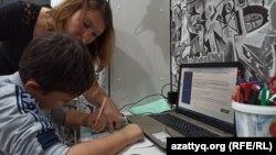 Twelve-year-old Roman Kaimashnikov and his mother, Tatiana Kaymashnikova, go over an online lesson together.