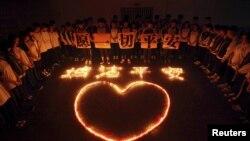 Студенты и учителя стоят вокруг свечей, зажженных в честь жертв взрывов в Тяньцзине.