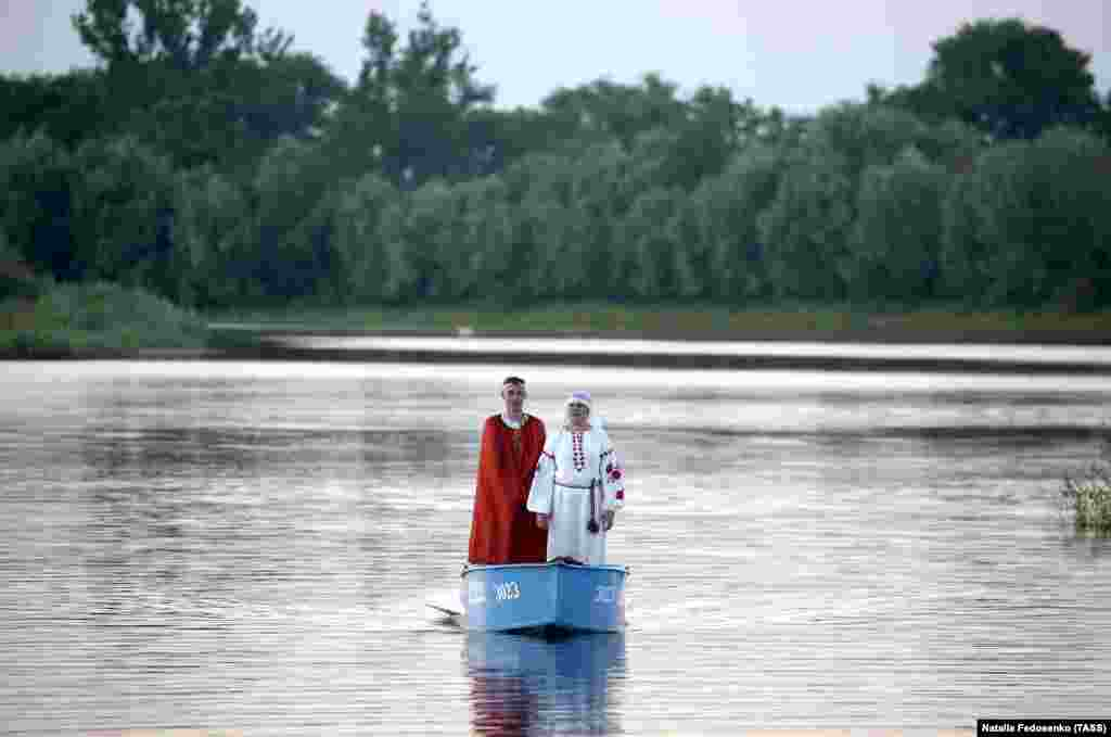 A couple in ethnic costumes stand in a boat on the Pripyat River in the town of Turau.