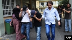 Turkish plainclothes police officers escort suspected members of the Islamic State (IS) group at a hospital for a medical check-up in Istanbul on July 24.