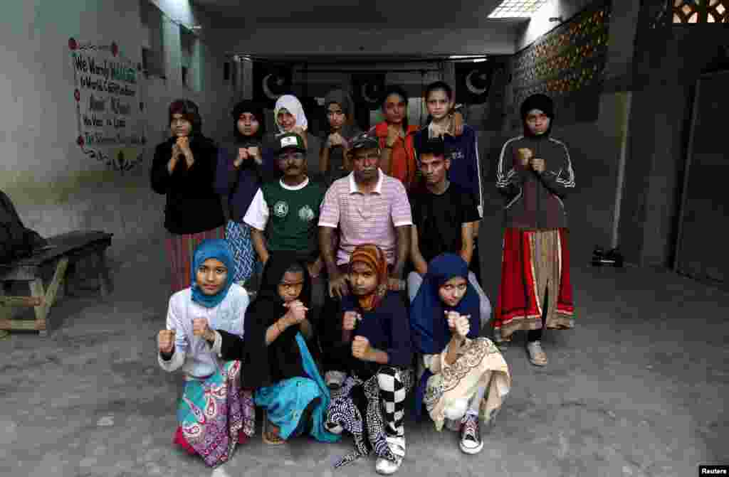 Girl trainees pose for a group photograph with their coach Yunus Qambrani and assistant coach Nadir at the boxing camp in Karachi.