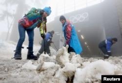 Рабочие убирают снег на лыжной трассе. Сочи, 17 февраля 2014 года.