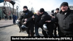 Police detain a protester at the march in Kyiv on March 8.