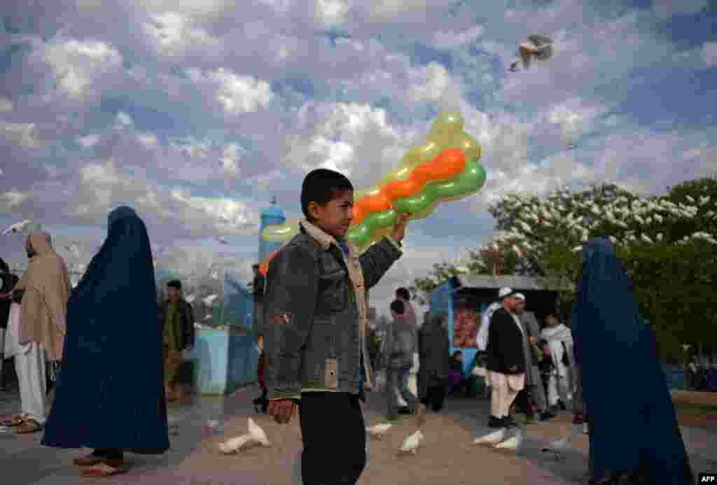 Afghan vendor Naweed, 13, sells balloons in the courtyard of the Hazrat-e Ali shrine, or Blue Mosque, in Mazar-e Sharif. (AFP/Farshad Usyan)
