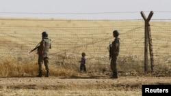 Турецкие военные и ребенок беженцев у границы Турции с Сирией.